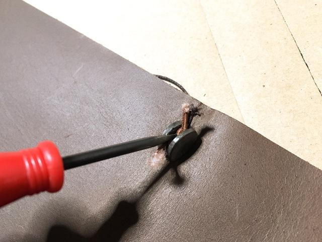 ゴムを結ぶことができたら、金具の切れ目に押し込んでいきます
